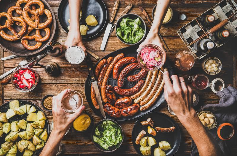 Flat-lay of Octoberfest dinner table with beer, snacks and people. Flat-lay of Octoberfest party dinner table with grilled meat sausages, German pretzel pastry stock images