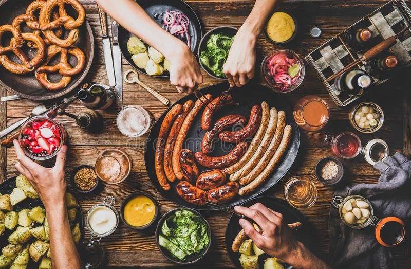 Bavarian sausages, snacks and beers for Octoberfest dinner party. Flat-lay of Octoberfest dinner table concept with grilled sausages, pretzel pastry, potatoes stock photo
