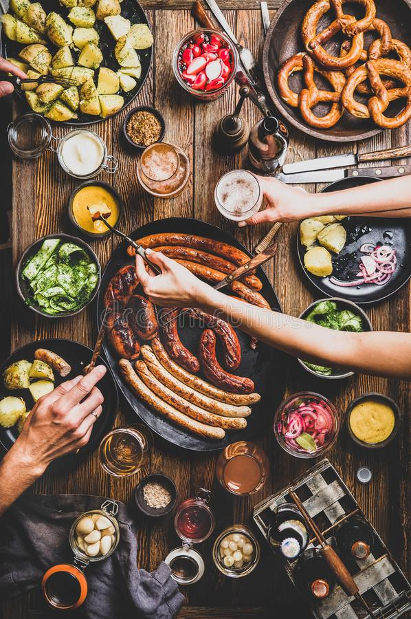 Octoberfest dinner table with beers, sausages, peoples hands with snacks. Flat-lay of Octoberfest dinner table with grilled sausages, pretzel pastry, potatoes royalty free stock image