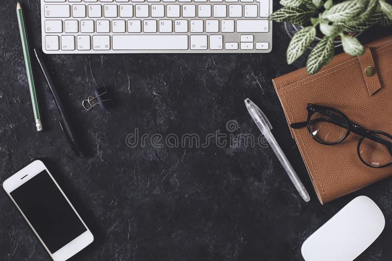 Flat lay. Office dark table with computer notepad, mouse, pen, p. Flat lay. Working place on dark table with copy space. Table with keyboard, computer, notepad stock image