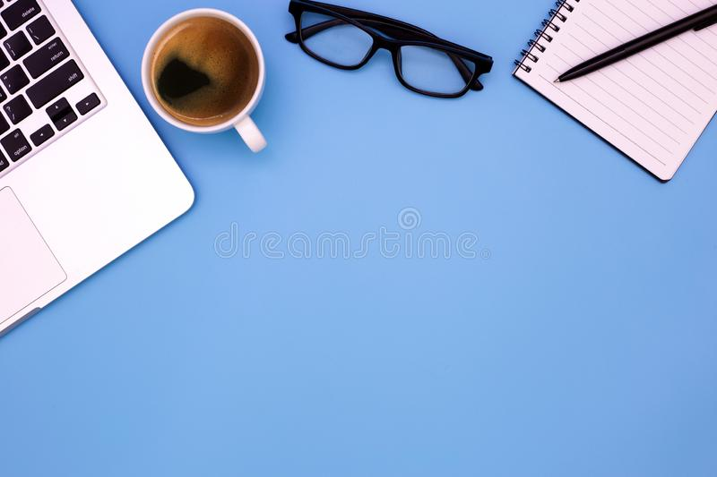 Flat lay Office desk table of modern workplace with laptop on blue table, top view laptop background and copy space on blue stock photo