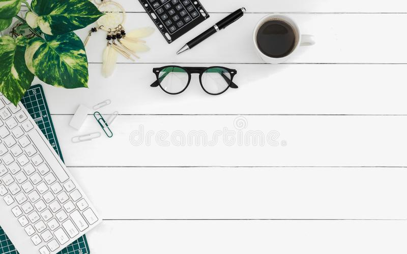 Flat lay of office desk work space table with computer wireless keyboard and stationary in home office on white wood table. Top royalty free stock image