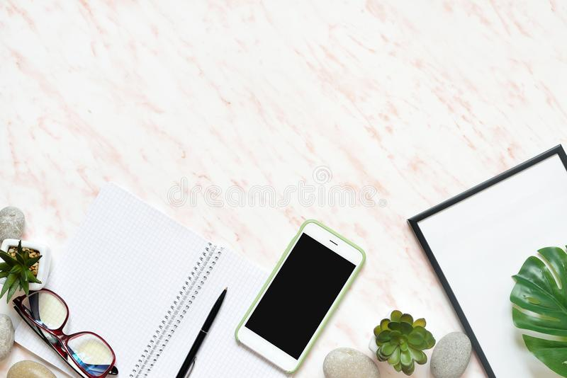 Flat lay office marble desk with phone, frame and notebook copy space background royalty free stock photography