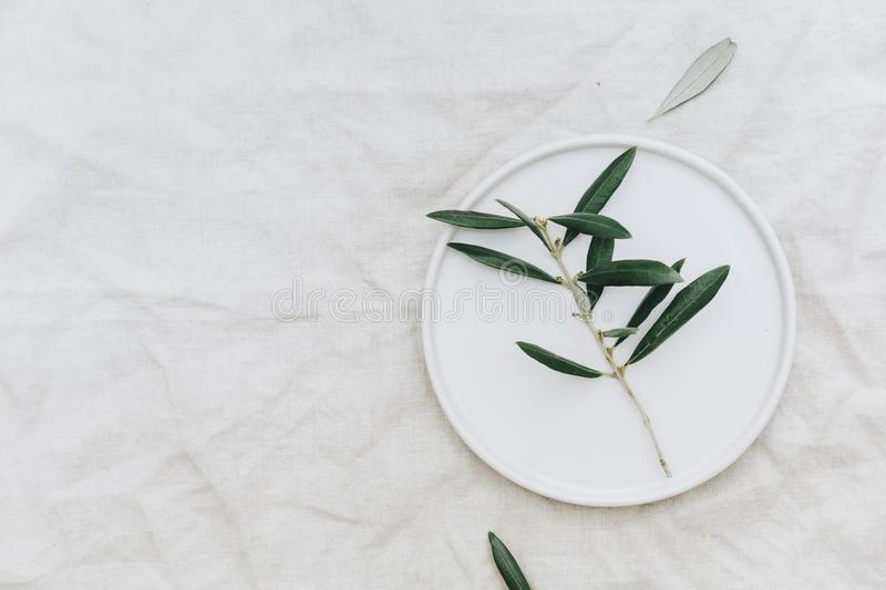 Flat lay olive branch on white plate over linen tablecloth. royalty free stock image
