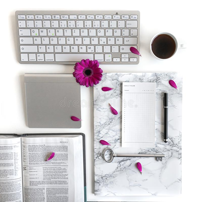Flat lay: open book, keyboard, coffee, black pen, to do list, silver and pink, purple, violette, red Gerbera flower with petals stock photos