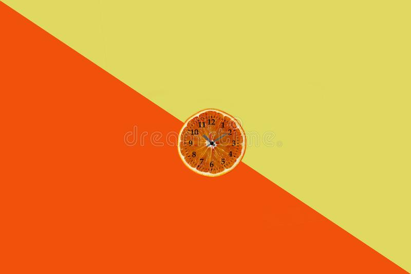 Flat lay of orange fruit slice with clock on yellow and orange paper background royalty free stock image