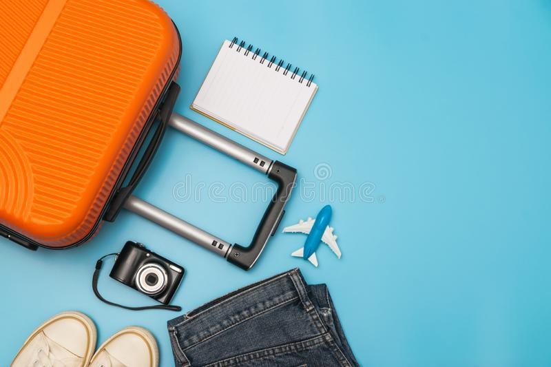 Flat lay orange suitcase with traveler accessories on soft blue background. travel, summer and holiday concept.  stock images