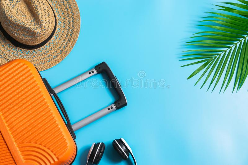 Flat lay orange suitcase with traveler accessories on soft blue background. travel, summer and holiday concept.  royalty free stock photos