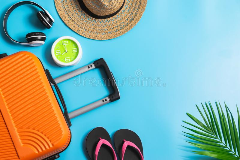 Flat lay orange suitcase with traveler accessories on soft blue background. travel, summer and holiday concept.  royalty free stock images