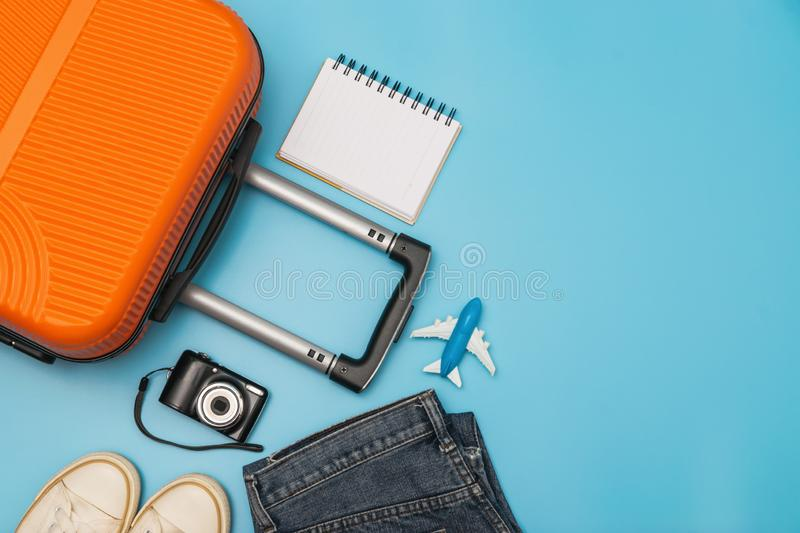Flat lay orange suitcase with traveler accessories on soft blue background. travel, summer and holiday concept.  stock image