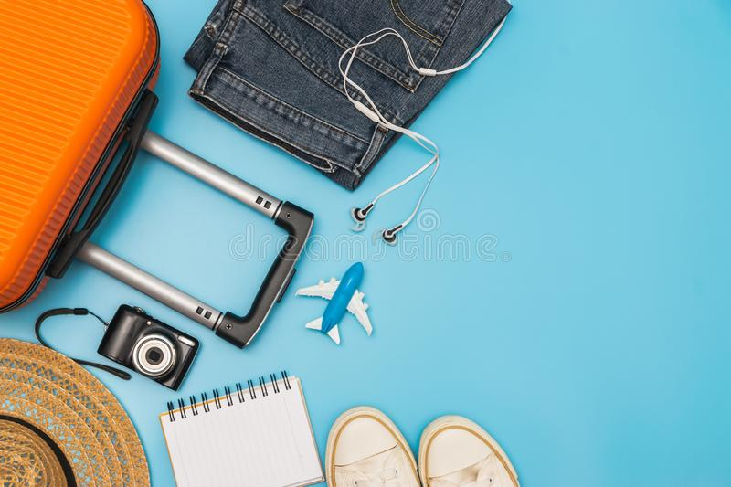 Flat lay orange suitcase with traveler accessories on soft blue background. travel, summer and holiday concept.  stock photography