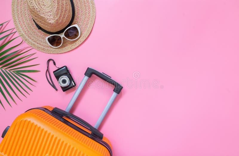 Flat lay orange suitcase with traveler accessories on soft pink background. travel, summer and holiday concept.  stock photo