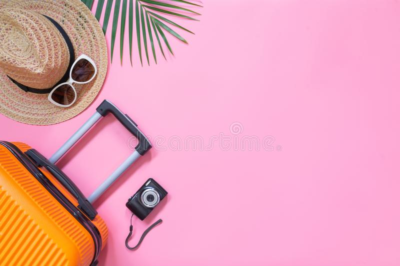 Flat lay orange suitcase with traveler accessories on soft pink background. travel, summer and holiday concept.  royalty free stock images