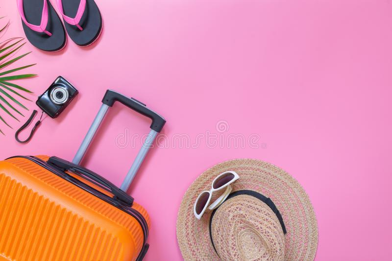 Flat lay orange suitcase with traveler accessories on soft pink background. travel, summer and holiday concept.  stock photography