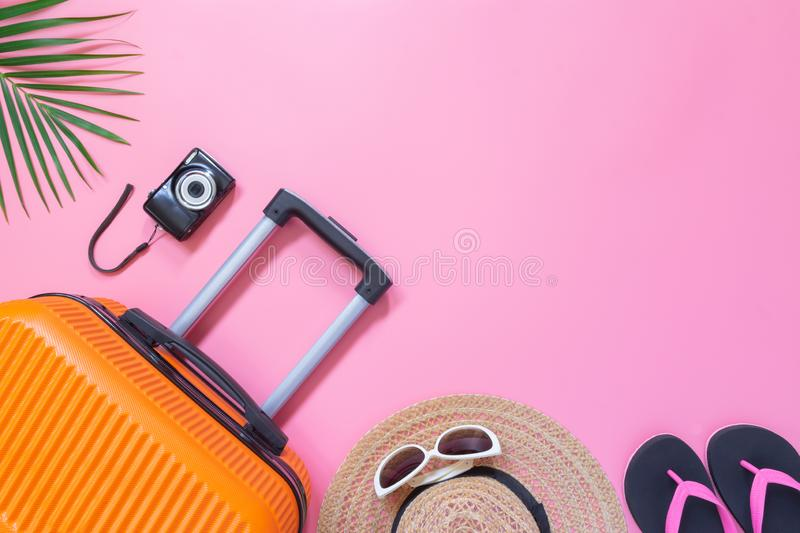 Flat lay orange suitcase with traveler accessories on soft pink background. travel, summer and holiday concept.  royalty free stock image