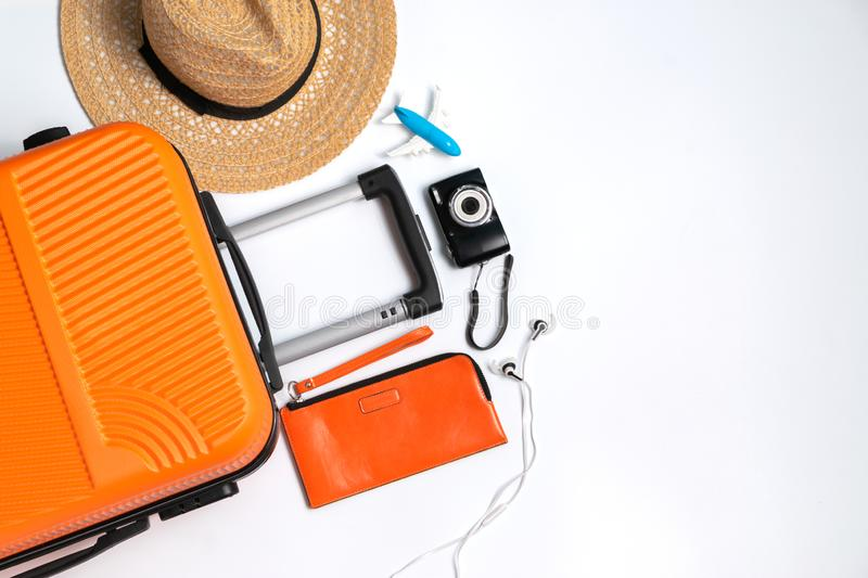 Flat lay orange suitcase with traveler accessories on white background. travel, summer and holiday concept.  royalty free stock image