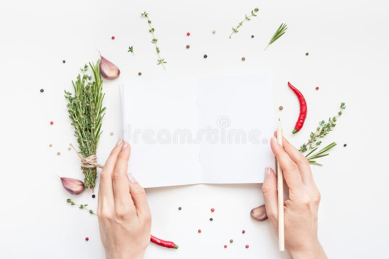 Blank notepad pages with greens herbs and spices. Flat lay overhead view blank notebook pages mockup text space invitation card on white background with greens stock photography