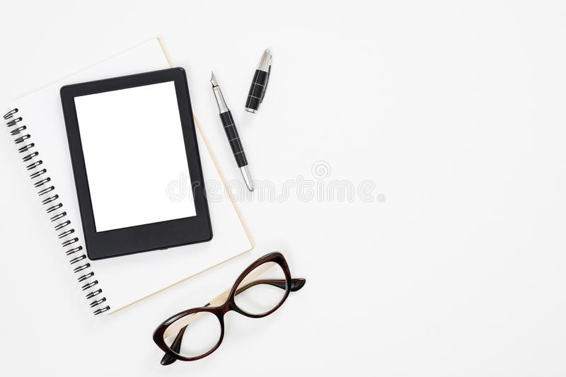 Flat lay paper notebook, e-book reader glasses on white background. Top view feminine diary, stationery and electronic device on. Home office desk royalty free stock photography