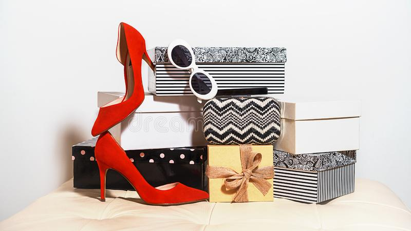Top view party outfit composition trendy female accessories red shoes sunglasses handbag clutch on carton boxes on white royalty free stock photos