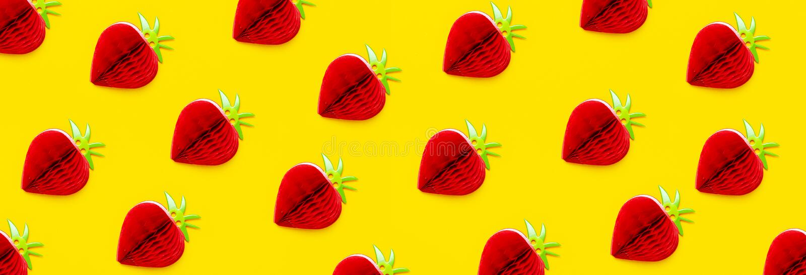 Flat lay Pattern bright sweet red strawberry of paper on yellow background top view copy space. Minimalistic creative summer food. Concept, origami paper fruit stock photo