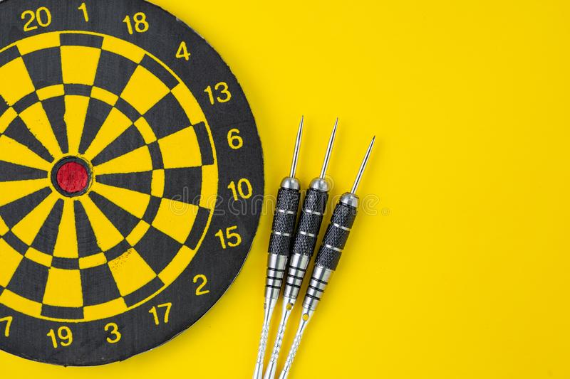 Flat lay of perfect black darts with dartboard on solid yellow background with copy space using as target and goals or three best royalty free stock photo