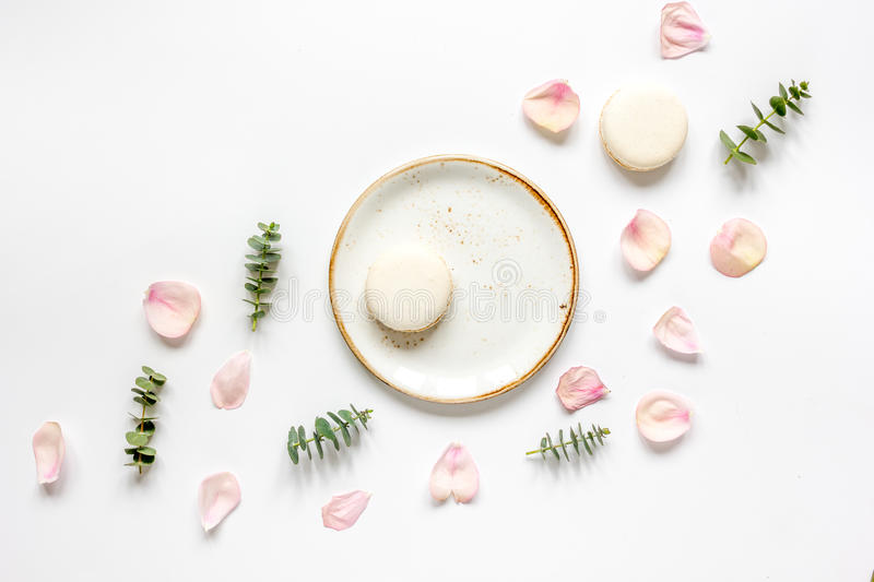 Flat lay with petals and macaroons on white background top view stock images
