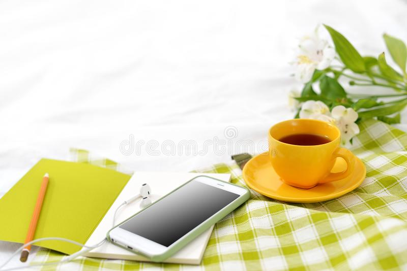 Flat lay phone, yellow cup of tea and flowers on white blanket with green napkin royalty free stock images