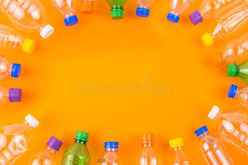 Circle plastic bottles frame with copy space. Flat lay photo, collection of empty clean plastic bottles with various colour caps arranged in circle frame on stock images