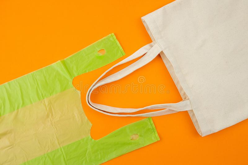 Eco bag vs plastic bag. Flat lay photo of green plastic bag compare to fabric tote bag on orange background as eco-friendly and sustainable lifestyle concept stock image