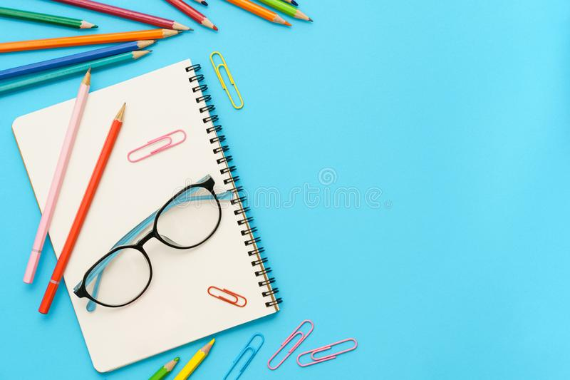 Flat lay photo of office desk with colorful pencil, Paper clip, Note book, Glasses, Top view of the copy space stock photography