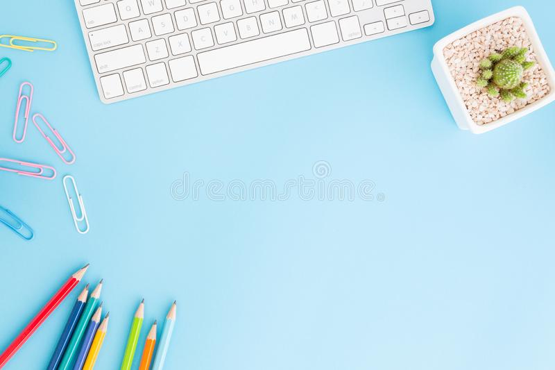 Flat lay photo of office desk with pencil and keyboard ,Top view workpace on blue background and copy space royalty free stock photography