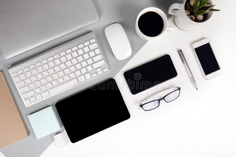 Flat lay photo of Office table with keyboard, notebook, digital tablet, mobile phone, Pencil, eyeglasses on modern two tone. White and grey background. Desktop stock images