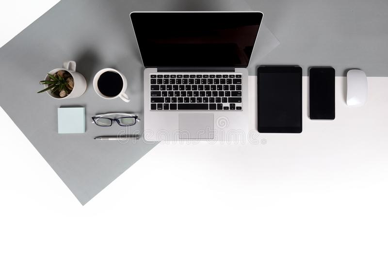 Flat lay photo of Office table with laptop computer, notebook, digital tablet, mobile phone on modern two tone background royalty free stock image