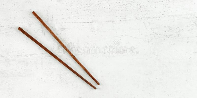 Flat lay photo - pair of dark wood chopsticks on white board. Wide banner for asian / chinese food, space for text on right.  stock images