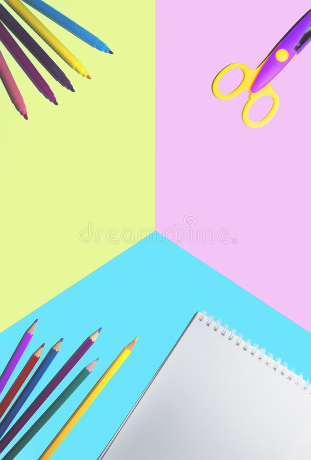 Flat lay picture of colored pencils, notepad and scissors lined on a smooth surface isolated background of halved in blue and pink. Color royalty free stock image