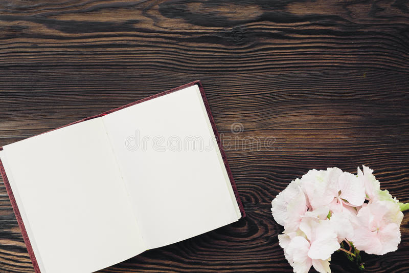 Flat lay pink flowers and diary on wooden background, top view. mock up. Flat lay pink flowers and a diary on a wooden background, top view. mock up stock photography