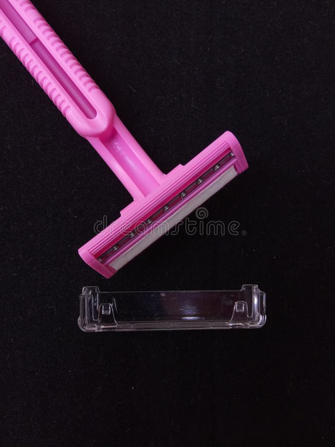 Flat Lay Pink Woman Shaver with transparent cap at Black Background. Photo Flat Lay Pink Woman Shaver with transparent cap at Black Background stock photography