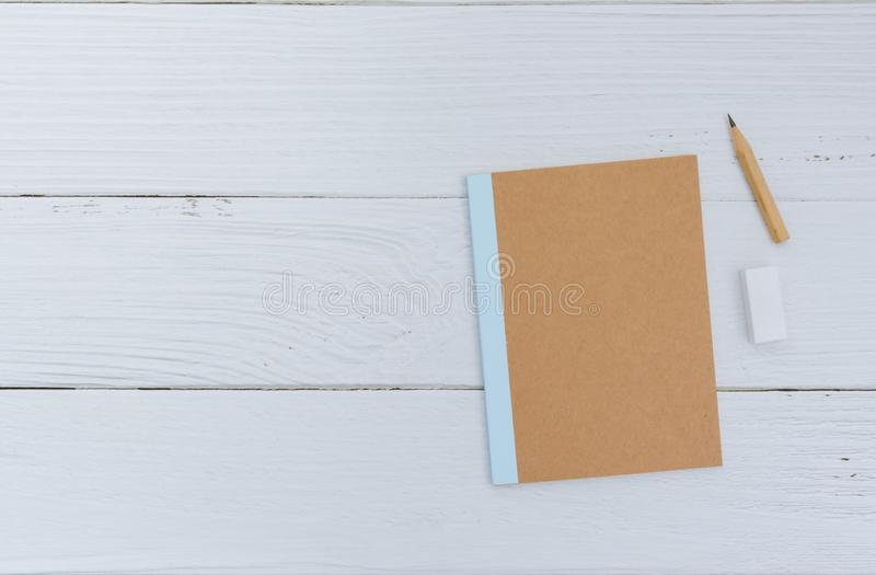 Flat lay of plain notebook with brown pencil and rubber on white background royalty free stock image