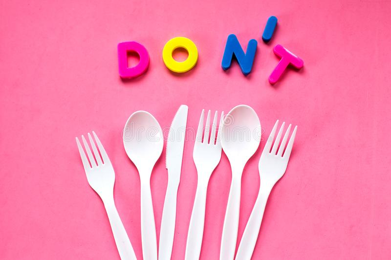 Flat lay of plastic white cutlery on pink background. Recycling concept. royalty free stock photos