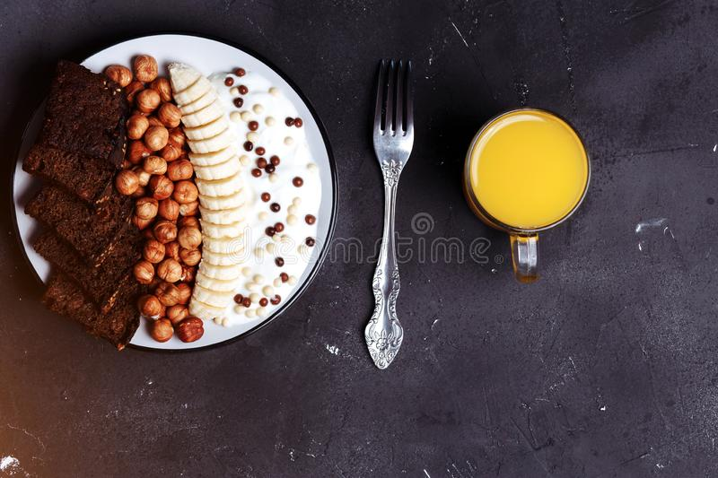 Flat lay of a plate of fruit, nuts, bread, yogurt and orange juice on the table on a black background with copy space. Healthy royalty free stock images