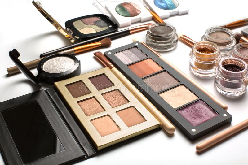 Flat lay of eyeshadow palettes, highlighters and cosmetic brushes on a white background. Flat lay of professional eyeshadow palettes, highlighters and cosmetic royalty free stock image