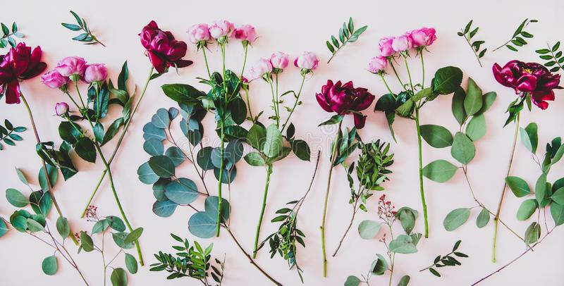 Flat-lay of purple peonies, pink roses and green branches royalty free stock photos