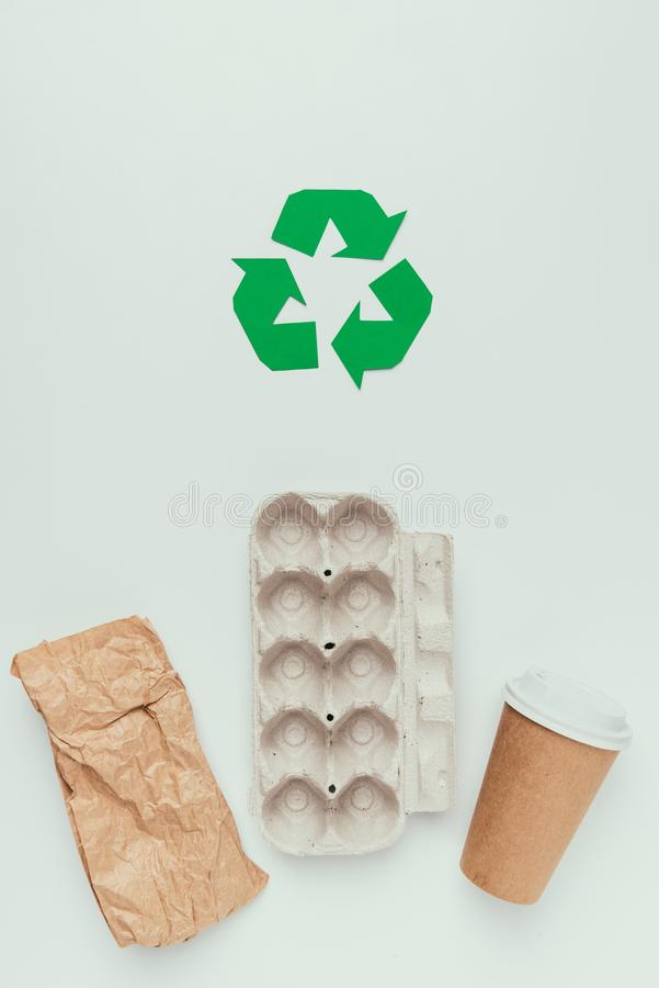 Flat lay with recycle sign and disposable trash. Isolated on grey stock photos