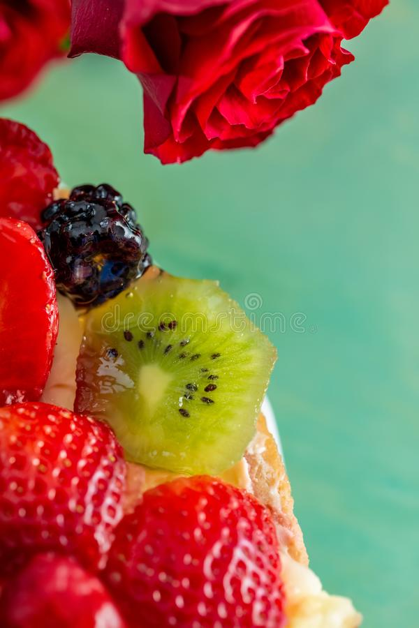 Flat-lay of red flowers roses and beautiful delicious sweet cake with berries on a green background. stock photography