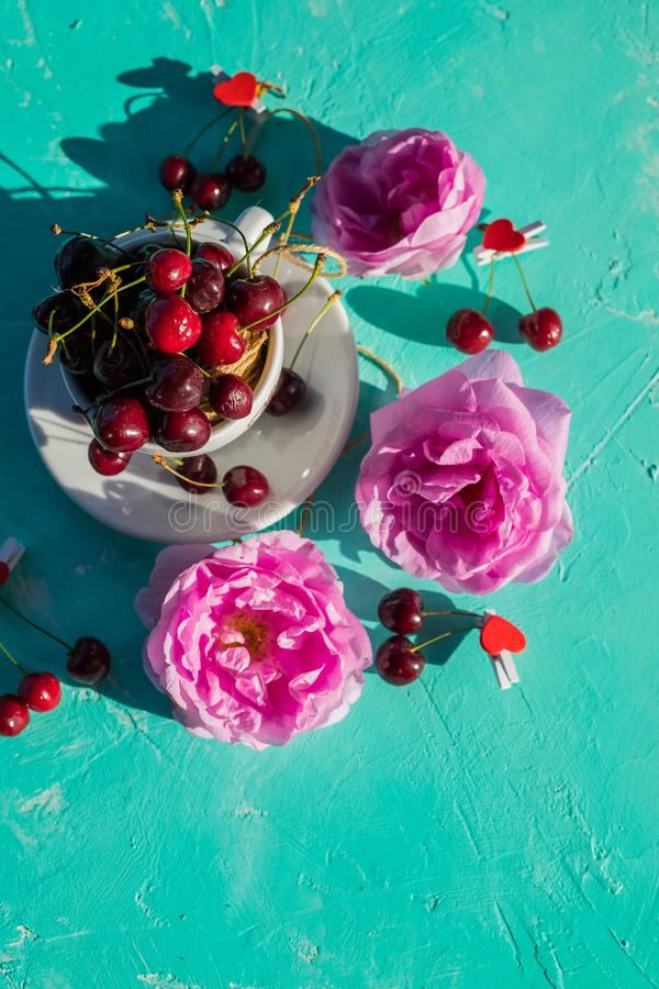 Flat lay of Red ripe sweet cherry in a white cup and pink roses on a green table in a summer garden.fresh berries and stock images