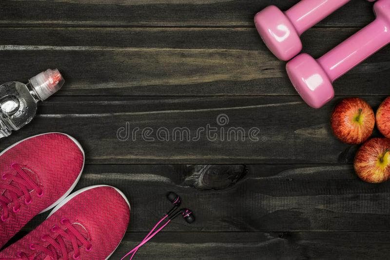 Flat lay of red sport shoes, dumbbells, earphones, bottle of water and apples on wood background. Active Healthy lifestyle, work royalty free stock photos