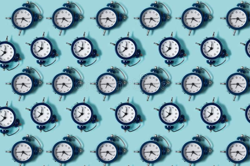 Flat lay retro beautiful new alarm clock on blue color background. Pattern. Top. View stock photos