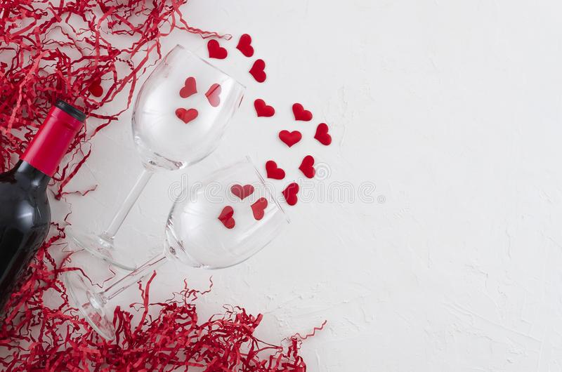 Flat lay romantic concept glasses and bottle of red wine on white background with hearts and red packing straw. View royalty free stock photos