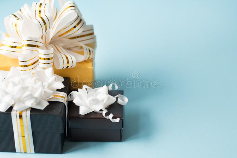 Flat lay of romantic gifts wrapped and decorated with bow on blue background with copy space . greeting card royalty free stock images