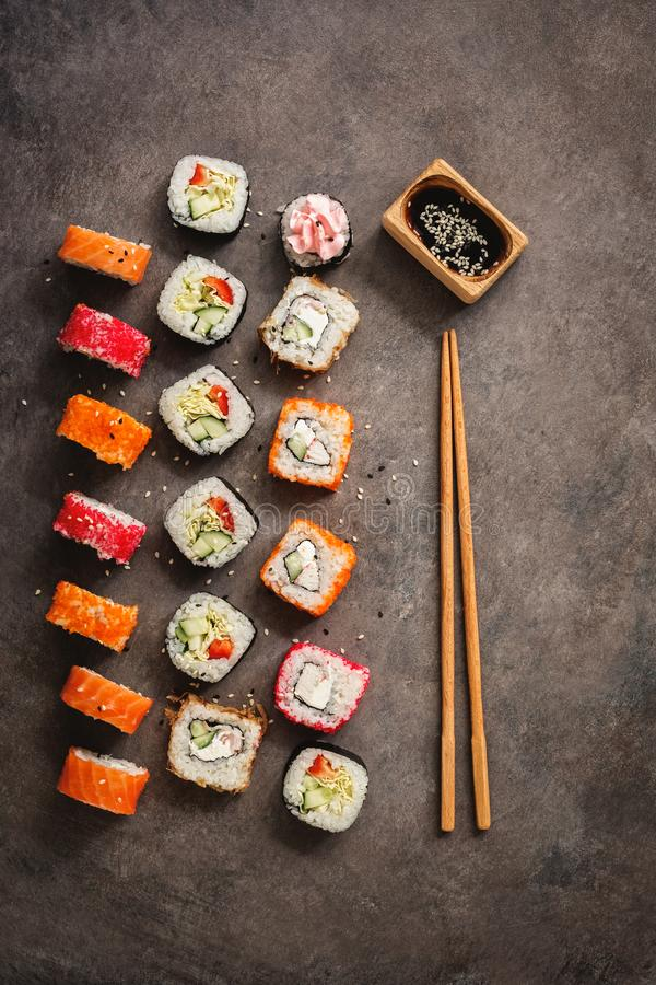 Flat lay rows of sushi rolls, soy sauce and chopsticks on a dark rustic background. View from above. Traditional asian food royalty free stock photo